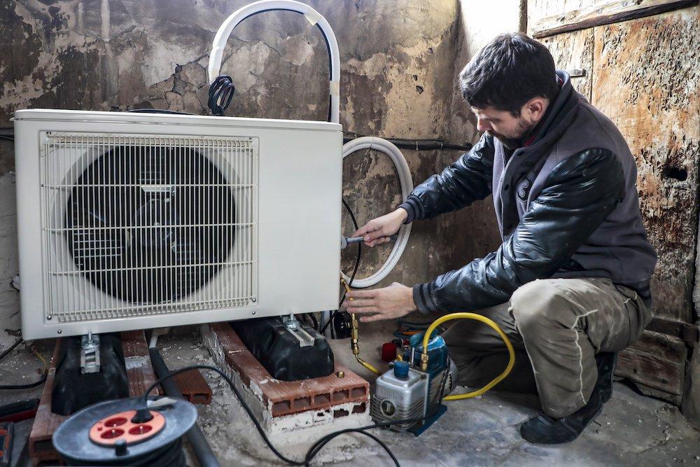 Technicien pose une pompe à chaleur